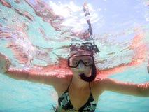 Schießen der jungen Frau im Wasser von unterhalb mit den offenen Armen mit Maske und Schnorchel in einem schönen Spiel von farbig stockbild