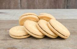Schieben Sie die Kekse, gefüllt mit Schokolade ein, setzen Sie an einen Holztisch lizenzfreies stockbild