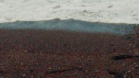 Schieber geschossen vom vulkanischen Mittelmeerstrand mit rotem Sand und menschlichem Abdruck-Abschluss-oben stock footage