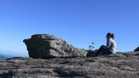 Schieber herauf die Frau, die auf Felsen sitzt stock video
