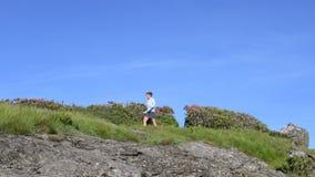 Schieber Pan Woman Hikes Through Rhodo und über Felsen stock footage