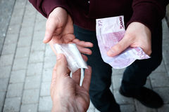 Schieber und Drogenabhängige, die Geld und Droge austauschen stockbilder