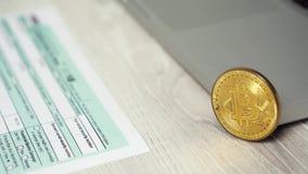 Schieberschuß von Bitcoin-Münze auf dem Computerlaptop nahe bei Einkommenssteuererklärungs-Rückerstattungs-Formkonzept 1040 Bitco stock video footage