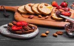 schiebt crostini mit Schokoladenmasse, große rote Erdbeere ein stockfotos