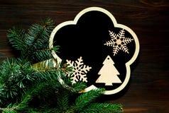 Schieferbrett mit hölzernen Feiertagsdekorationen und Weihnachtshintergrund mit Tannenbaumasten auf hölzernem Hintergrund kopiere stockbild