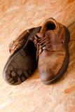 Schiefwinkliges Foto von alten braunen Lederschuhen auf OSB-Brett Stockbild