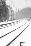 Schienen im nebeligen Schnee Stockfotografie