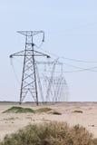 Schiera dei piloni elettrici su un cielo libero in deserto Immagini Stock Libere da Diritti