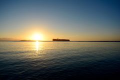 Schiff auf dem Horizont bei Sonnenaufgang Stockfoto