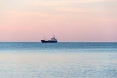 Schiff auf dem Horizont bei Sonnenuntergang Stockfotografie