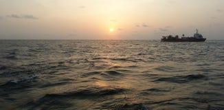 Schiff auf dem Ozean während des Sonnenuntergangs lizenzfreies stockbild