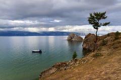 Schiff auf dem See, der durch Berge umgibt Lizenzfreie Stockfotos