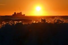 Schiff im Meer bei Sonnenuntergang lizenzfreies stockbild