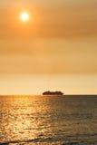 Schiff in Meer mit goldener Sonne Stockfoto