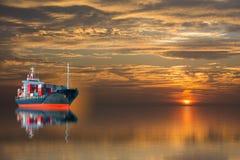 Schiff mit Behälter auf Sonnenuntergang Stockfotografie