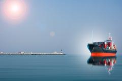 Schiff mit Behälter fahren gegen Dock Stockfoto