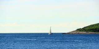 Schiff segelt um Insel-Kap Stockfotografie