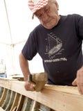 Schiffbauer arbeitet mit einem Ziehmesser Stockbild