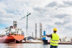 Schiffbauingenieur, der Dokumente an der Dockseite in einem Hafen überprüft stockfotos