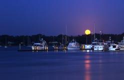 Schiffe im Hafen am moonset an der Dämmerung mit Reflexion auf ruhigem Wasser Lizenzfreies Stockbild