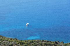 Schiffe verankerten vor der Küste auf dem blauen ruhigen See Stockbilder