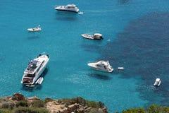 Schiffe verankerten vor der Küste auf dem blauen ruhigen See Stockfotografie