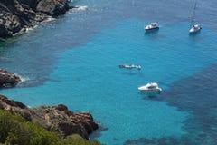 Schiffe verankerten vor der Küste auf dem blauen ruhigen See Lizenzfreies Stockfoto