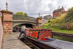 Schiffer, der ein Narrowboat, Dudley, West Midlands manövriert Lizenzfreies Stockbild