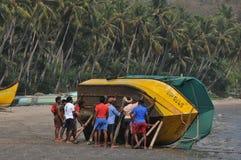 Schiffer, die das Boot zum Meer drücken lizenzfreies stockbild