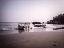 Schiffer, die mit ihrem Boot im Strand warten stockbilder