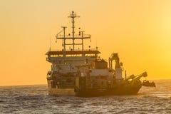 Schiffs-Bagger-Morgen färbt Ozean Lizenzfreie Stockfotos