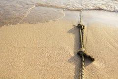 Schiffstau mit Knoten auf feinem Sand Lizenzfreie Stockbilder