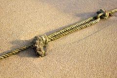 Schiffstau mit Knoten auf feinem Sand Lizenzfreie Stockfotografie