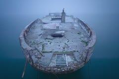 Schiffswrack im Nebel und im ruhigen Wasser Lizenzfreie Stockfotografie
