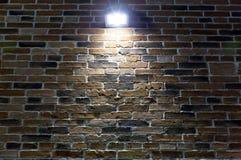Schijnwerper op rode bakstenen muur bij nacht royalty-vrije stock fotografie
