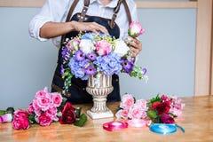 Schikkend kunstbloemen bekleed decoratie thuis, het Jonge werk die van de vrouwenbloemist het organiseren van diy kunstbloem, amb stock afbeelding