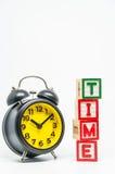 Schikt het houten blok van het TIJDwoord in verticale stijl met zwarte retro wekker op witte achtergrond en selectieve nadruk Royalty-vrije Stock Foto