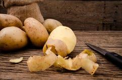 Schil verse aardappels op rustieke houten achtergrond Ruwe organische pot Royalty-vrije Stock Foto's