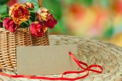 schild de la cartulina y la cesta con las rosas Foto de archivo