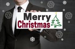 Schild der frohen Weihnachten wird vom Geschäftsmann gehalten Lizenzfreies Stockbild