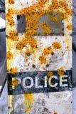 Schild van een politieagent met paintballpatronen wordt gebombardeerd met verf die Royalty-vrije Stock Afbeeldingen