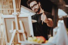 Schilder Holds Paintbrush Looking bij Stilleven stock fotografie