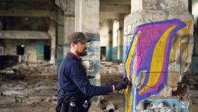 Schilder van de jonge mensen werkt de professionele graffiti de binnen verlaten bouw, schildert hij met de verf van het nevelaëro stock footage