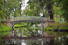 Schilderachtig landschap met oude brug over stroom in het park Royalty-vrije Stock Afbeeldingen