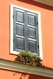 Schilderachtig uitstekend venster met gesneden houten zonneblinden en bloemen in heldere oranje muur stock afbeeldingen