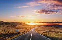 Schilderachtige die landweg, in de zomerzonsopgang wordt gemodelleerd stock afbeelding