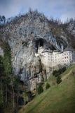 Schilderachtige die mening van het Predjama-Kasteel in het midden van een torenhoge klip in Slovenië wordt gesitueerd Stock Fotografie