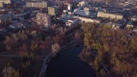 Schilderachtige lucht4k-hommelvlucht over kalme kleine stadscityscape met het meer van de spiegeloppervlakte in park bij zonsonde stock footage
