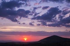 Schilderachtige purpere zonsondergang over heuvels Stock Fotografie