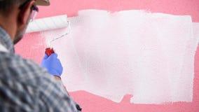 Schilderarbeider die de roze muur met witte verf schilderen De bouw stock video